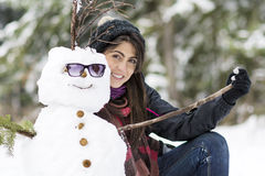 Smiling young woman hugging   snowman. In a snowy garden Royalty Free Stock Photos