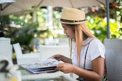 Free Smiling Young Woman In A Restaurant With The Menu In Hands, Young Woman Choosing Royalty Free Stock Photo - 163384995