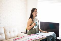 Cute woman ironing shirt in living room. Smiling young woman ironing clothes with electric iron at home Stock Image