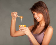 Smiling young woman with jar of honey Stock Images