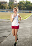 Smiling young woman jogging, training outdoors Stock Photo
