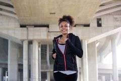 Smiling young woman jogging in urban environment Stock Image