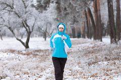Smiling young woman jogging at winter park. Royalty Free Stock Photo