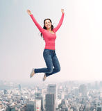 Smiling young woman jumping in air Stock Photography
