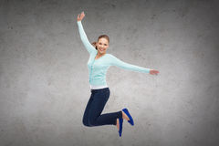 Smiling young woman jumping in air Stock Photo