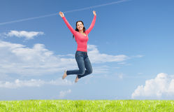 Smiling young woman jumping in air Stock Image