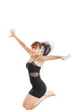 Smiling young woman jumping in the air with open arms Royalty Free Stock Image