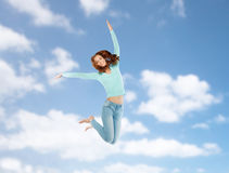 Smiling young woman jumping in air over blue sky Royalty Free Stock Photography