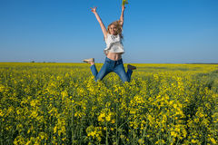 Smiling young woman jumping in a field Stock Image