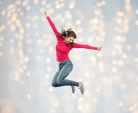 Smiling young woman jumping over holidays lights Stock Images