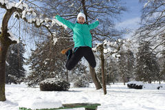 Smiling young woman jumping on a sunny winter day Royalty Free Stock Images