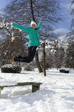Smiling young woman jumping on a sunny winter day Stock Photo
