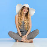 Smiling Young Woman In Jumpsuit, White Sun Hat And High Heels Is Sitting With Legs Crossed Royalty Free Stock Images