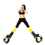 Smiling young woman in kangoo jumps shoes showing fingers up Royalty Free Stock Photos