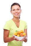 Smiling young woman keeping full bowl with apricot Royalty Free Stock Photos