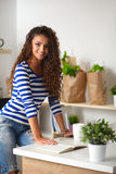 Smiling young woman in the kitchen,  on Royalty Free Stock Photos