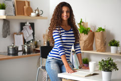 Smiling young woman in the kitchen,  on Stock Photography