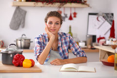 Smiling young woman in the kitchen,  on Royalty Free Stock Photography