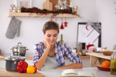 Smiling young woman in the kitchen,  on Royalty Free Stock Photo