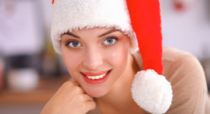 Smiling young woman in the kitchen,  on christmas background Royalty Free Stock Photos