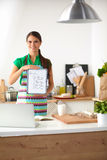 Smiling young woman in the kitchen, isolated on Royalty Free Stock Photos