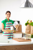 Smiling young woman in the kitchen, isolated on Stock Photos