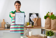 Smiling young woman in the kitchen, isolated on Royalty Free Stock Photography