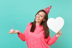 Smiling young woman in knitted pink sweater birthday hat hold in hand cake with candle, white heart with copy space. Isolated on blue turquoise background stock images