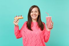 Smiling young woman in knitted pink sweater holding in hands eclair cake, plastic cup of cola or soda isolated on blue. Smiling young woman in knitted pink stock images