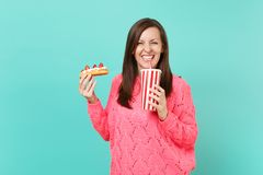 Smiling young woman in knitted pink sweater holding in hands eclair cake, plastic cup of cola or soda isolated on blue. Smiling young woman in knitted pink stock photography