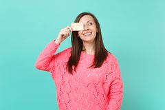 Smiling young woman in knitted pink sweater looking up, covering eye with credit card in hand isolated on blue turquoise. Wall background, studio portrait stock photography