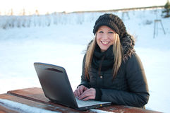 Smiling young woman with laptop in winter Royalty Free Stock Photos
