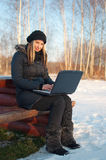 Smiling young woman with laptop in winter Royalty Free Stock Photo