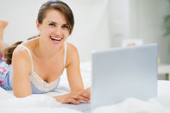 Smiling young woman laying on bed and using laptop Royalty Free Stock Images