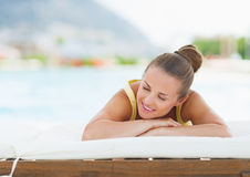 Smiling young woman laying on chaise-longue Royalty Free Stock Images