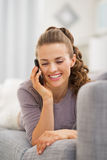Smiling young woman laying on couch and talking mobile phone Royalty Free Stock Photos