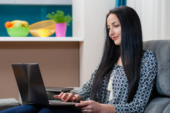 Smiling young woman laying on couch and using laptop Stock Photo