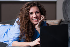 Smiling young woman laying on couch and using laptop. Stock Image
