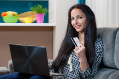 Smiling young woman laying on couch and using laptop Royalty Free Stock Photography