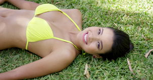 Smiling young woman laying on grass stock footage