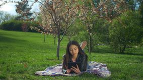 Smiling young woman laying on lawn with tablet pc stock video footage