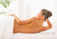 Smiling young woman laying on massage table. rear view Stock Photos