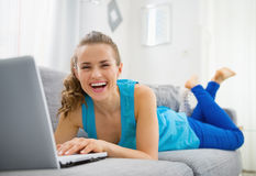 Smiling young woman laying on sofa and using laptop royalty free stock photos