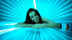 Smiling young woman laying on solarium Stock Photo