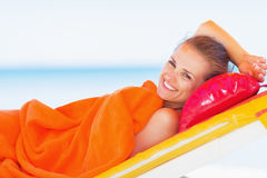 Smiling young woman laying on sunbed Royalty Free Stock Images
