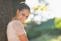 Smiling young woman lean against tree Royalty Free Stock Photo