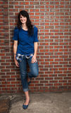 Smiling Young Woman Leaning Against Red Brick Wall Royalty Free Stock Images