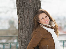 Smiling young woman leaning against tree in winter park Stock Photo