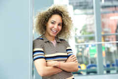 Smiling young woman leaning against wall with arms crossed Royalty Free Stock Image
