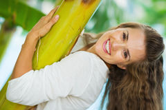 Smiling young woman leaning on tropical palm Stock Image